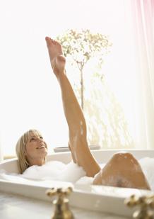 Imagem de uma mulher numa banheira, com uma perna esticada. A imagem ilustra que é possível descontrair e viver normalmente, mesmo com o período.