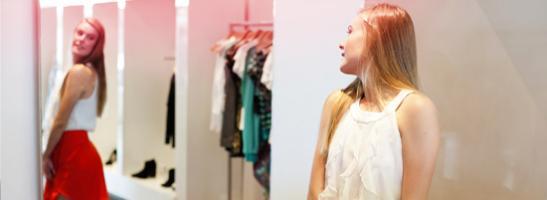 Rapariga muito jovem em frente ao espelho a experimentar roupa nova. A imagem ilustra como o corpo de uma jovem muda durante a puberdade.