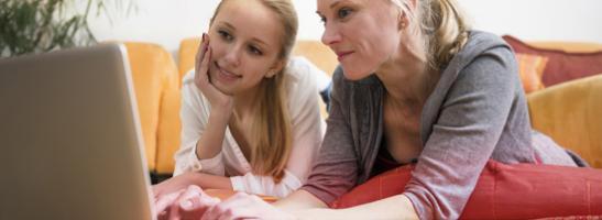 Imagem de mãe e filha a usarem o computador juntas. A imagem ilustra a importância da comunicação e de ajudar a sua filha a encontrar a informação certa.