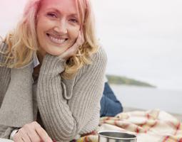 Imagem de uma mulher de meia idade, a sorrir.